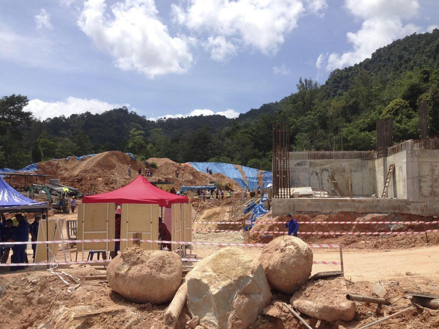 A rescue operation is conducted at a construction site after a landslide in Penang, Malaysia, Saturday, Oct. 21, 2017. Fire and rescue official Mohamad Rizuan Ramli said a 10-meter high hill slope crashed down at the construction site early Saturday. (AP Photo/Peter Ewe)