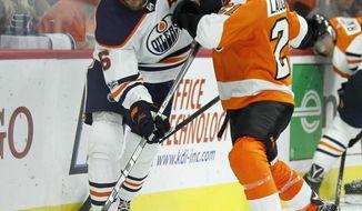 Edmonton Oilers' Adam Larsson, left, pushes aside Philadelphia Flyers' Scott Laughton behind the Edmonton net during the second period of an NHL hockey game against the, Saturday, Oct. 2119, 2017, in Philadelphia. (AP Photo/Tom Mihalek)