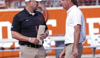 Texas head coach Tom Herman, left, talks with Oklahoma State head coach Mike Gundy, right, before the start of an NCAA college football game, Saturday, Oct. 21, 2017, in Austin, Texas. (AP Photo/Michael Thomas)