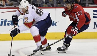 Florida Panthers left wing Jamie McGinn (88) skates with the puck past Washington Capitals defenseman Madison Bowey (22) during the first period of an NHL hockey game, Saturday, Oct. 21, 2017, in Washington. (AP Photo/Nick Wass)