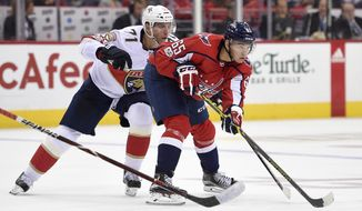 Washington Capitals left wing Andre Burakovsky (65), of Austria, skates with the puck in front of Florida Panthers right wing Radim Vrbata, back, of the Czech Republic, during the second period of an NHL hockey game, Saturday, Oct. 21, 2017, in Washington. (AP Photo/Nick Wass)
