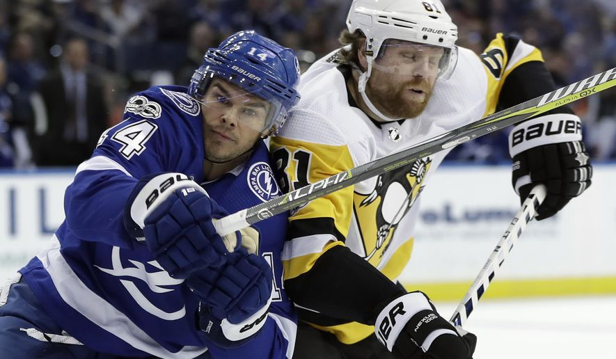 Tampa Bay Lightning left wing Chris Kunitz (14) checks Pittsburgh Penguins right wing Phil Kessel (81) during the second period of an NHL hockey game Saturday, Oct. 21, 2017, in Tampa, Fla. (AP Photo/Chris O'Meara)