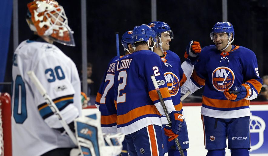 New York Islanders' Anders Lee, second from right, is congratulated by teammates after scoring a goal on San Jose Sharks goalie Aaron Dell in the second period of an NHL hockey game, Saturday, Oct. 21, 2017, in New York. (AP Photo/Adam Hunger)