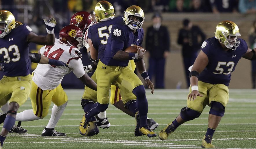 Notre Dame quarterback Brandon Wimbush breaks through the Southern California defense as he scrambles during the first half of an NCAA college football game, Saturday, Oct. 21, 2017, in South Bend, Ind. (AP Photo/Carlos Osorio)