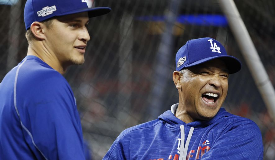 FILE - In this Oct. 13, 2016, file photo, Los Angeles Dodgers manager Dave Roberts, right, jokes with shortstop Corey Seager during batting practice before Game 5 of baseball's National League Division Series against the Washington Nationals at Nationals Park in Washington. The Dodgers earned a four-day break before the World Series with their quick resolution of the NLCS. (AP Photo/Pablo Martinez Monsivais, File)