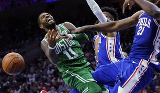 Boston Celtics' Kyrie Irving (11) gets his shot blocked by Philadelphia 76ers' Joel Embiid (21) in the second half of an NBA basketball game, Friday, Oct. 20, 2017, in Philadelphia. (AP Photo/Michael Perez)