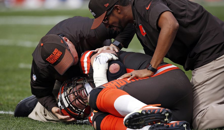 Trainers, top, check Cleveland Browns tackle Joe Thomas after Thomas was hurt in the second half of an NFL football game against the Tennessee Titans, Sunday, Oct. 22, 2017, in Cleveland. (AP Photo/Ron Schwane)