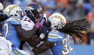 Denver Broncos running back C.J. Anderson, middle, is tackled by Los Angeles Chargers free safety Tre Boston, right, and strong safety Jahleel Addae during the second half of an NFL football game Sunday, Oct. 22, 2017, in Carson, Calif. (AP Photo/Jae C. Hong)
