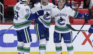 Vancouver Canucks left wing Sven Baertschi (47), of Switzerland, center, celebrates his goal against the Detroit Red Wings with center Bo Horvat (53) and defenseman Troy Stecher, right, during the first period of an NHL hockey game Sunday, Oct. 22, 2017, in Detroit. (AP Photo/Duane Burleson)