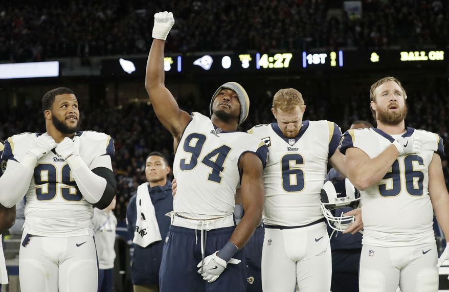 Los Angeles Rams outside linebacker Robert Quinn (94) raises his fist in the air during the playing of the U.S. national anthem before an NFL football game against Arizona Cardinals at Twickenham Stadium, in London, Sunday Oct. 22, 2017. (AP Photo/Matt Dunham)