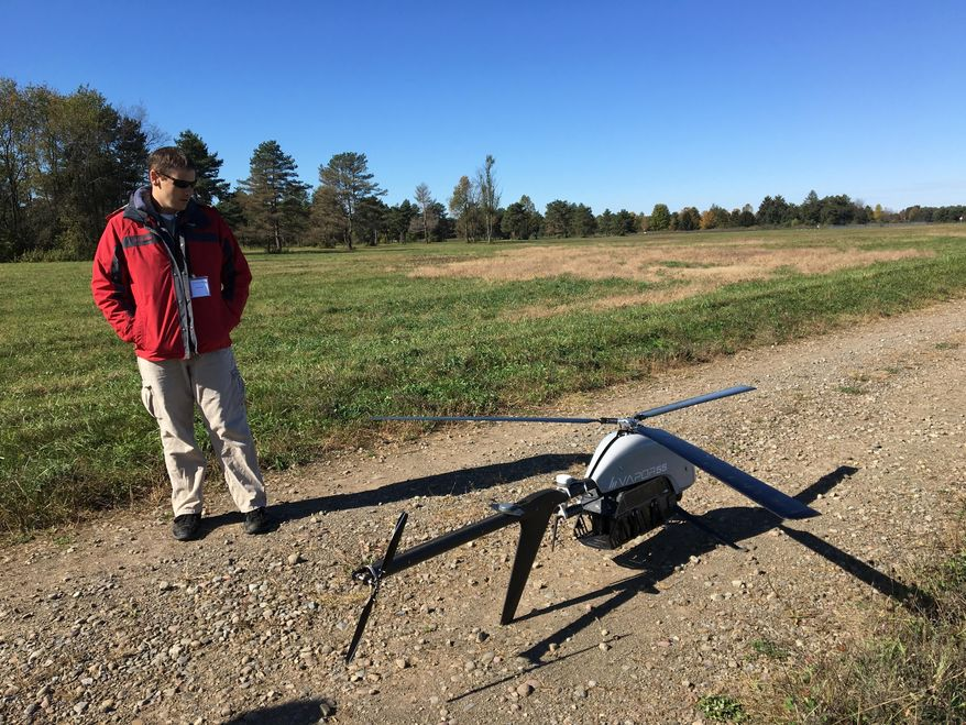 In this Oct. 17, 2017 photo, Nick Brown, a drone pilot for Pulse Aerospace of Lawrence, Kan., stands beside a Pulse Vapor unmanned aircraft at Griffiss International Airport in Rome, N.Y. New York is investing $30 million in a 50-mile drone testing corridor between Rome and Syracuse for drone research and development. (AP Photo/Mary Esch)