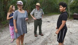 In this Oct. 4, 2017 photo, Craig Morris, center, a National Park Ranger at Fort Caroline National Memorial, meets a family from Jupiter, Fla., who stopped to visit the fort at Robert Gallegos-Duran's, right, insistence as they passed through town in Jacksonville, Fla. (Bruce Lipsky/The Florida Times-Union via AP)