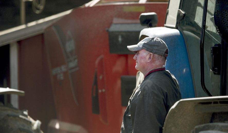 In a Tuesday, Oct. 17, 2017 photo, Jeff McNally, right, watches as a fellow Milton, Wis. farmer dumps high moisture corn into a gravity box in Milton, Wis. Farmers from the community helped Jeff with farm work after the recent death of his father, Tom McNally. (Angela Major/The Janesville Gazette via AP)