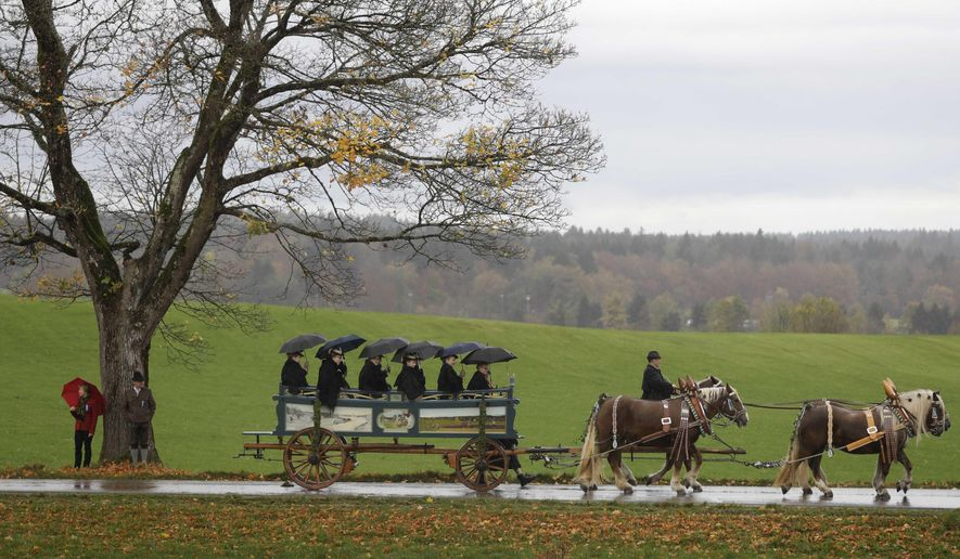 Women in their costumes of the region sit in a horse-drawn carriage during the traditional Leonhardi pilgrimage in Warngau, Germany, Sunday, Oct. 22, 2017. The annual pilgrimage honors St. Leonhard, patron saint of the highland farmers for horses and livestock. (AP Photo/Matthias Schrader)