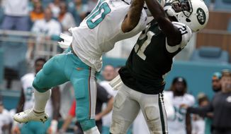 Miami Dolphins wide receiver Kenny Stills (10) attempts to hold onto a pass as New York Jets cornerback Morris Claiborne (21) defends, during the second half of an NFL football game, Sunday, Oct. 22, 2017, in Miami Gardens, Fla. (AP Photo/Lynne Sladky)