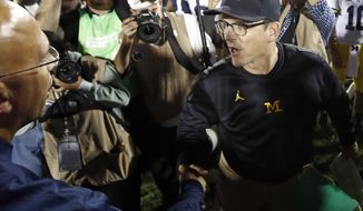 Michigan coach Jim Harbaugh, right, shakes hands with Penn State coach James Franklin at the end of an NCAA college football game in State College, Pa., Saturday, Oct. 21, 2017. Penn State won 42-13. (AP Photo/Chris Knight)