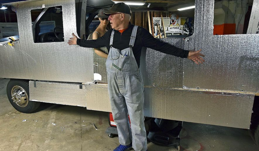 In this Tuesday, Oct. 17, 2017 photo, Jeff Daly stands in front of his latest automotive project in his studio in Astoria, Ore. Daly is currently remodeling an historic train he bought several years ago to travel on an old RV chasis to be used in local parades and other functions. (Colin Murphey /Daily Astorian via AP)