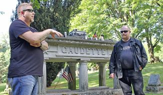 In this June 28, 2017 photo, Washington Abnormal Research Network (WARN) investigators Travis Fletcher, left, and Brian Lee explain how they use various devices to listen and watch for spirits or ghosts at Bay View Cemetery in Bellingham, Wash. (Kera Wanielista/Skagit Valley Herald via AP)