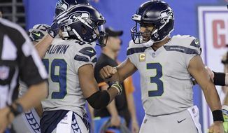 Seattle Seahawks quarterback Russell Wilson, right, celebrates with Doug Baldwin after scoring a touchdown during the second half of an NFL football game against the New York Giants, Sunday, Oct. 22, 2017, in East Rutherford, N.J. (AP Photo/Bill Kostroun)