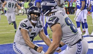 Seattle Seahawks quarterback Russell Wilson, left, celebrates with Jimmy Graham after Graham caught a touchdown pass during the second half of an NFL football game against the New York Giants, Sunday, Oct. 22, 2017, in East Rutherford, N.J. (AP Photo/Bill Kostroun)