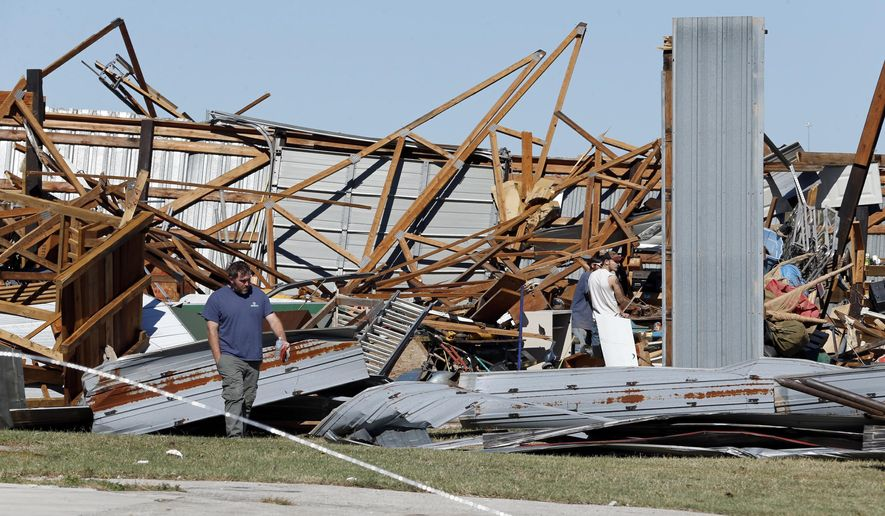 People look at damaged buildings near Norman, Okla., Sunday, Oct. 22, 2017. Several businesses were damaged by an apparent tornado that struck near I35 and Highway 9 on Saturday night. An overnight batch of severe storms spawned a tornado that tore part of a casino roof off in central Oklahoma and downed power lines and trees throughout the state, emergency managers said Sunday. (Steve Sisney/The Oklahoman via AP)
