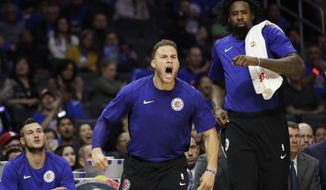 Los Angeles Clippers' Blake Griffin, center, and DeAndre Jordan, right, react to a dunk by Montrezl Harrell during the second half of an NBA basketball game against the Phoenix Suns on Saturday, Oct. 21, 2017, in Los Angeles. The Clippers won 130-88. (AP Photo/Jae C. Hong)