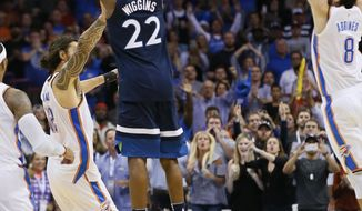 Minnesota Timberwolves guard Andrew Wiggins (22) shoots the game winning shot between Oklahoma City Thunder center Steven Adams (12) and guard Alex Abrines (8) in the fourth quarter of an NBA basketball game in Oklahoma City, Sunday, Oct. 22, 2017. Minnesota won 115-113. (AP Photo/Sue Ogrocki)