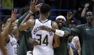 Milwaukee Bucks' Giannis Antetokounmpo is swarmed by teammates at the end of an NBA basketball game against the Portland Trail Blazers, Saturday, Oct. 21, 2017, in Milwaukee. (AP Photo/Tom Lynn)