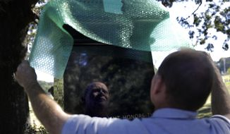 In this Friday, Oct. 20, 2017 photo, a monument to honor African-Americans who were buried in unmarked graves in the previously segregated Alta Vista Cemetery is wrapped by cemetery superintendent Tommy Casper after being displayed for a photo in Gainesville, Ga. The previously unmarked graves of more than 1,100 black souls buried in the cemetery will be honored with a memorial to be dedicated Sunday. Recently, the city discovered the extent of the unmarked graves using ground-penetrating radar. (AP Photo/David Goldman)