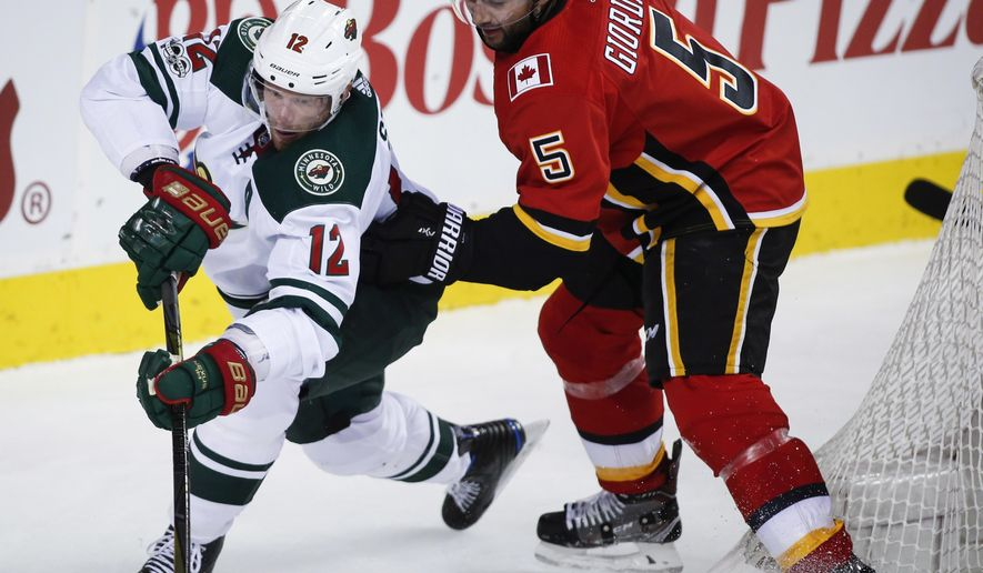 Minnesota Wild's Eric Staal, left, tries to get past Calgary Flames' Mark Giordano behind the net during the second period of an NHL hockey game Saturday, Oct. 21, 2017, in Calgary, Alberta. (Jeff McIntosh/The Canadian Press via AP)