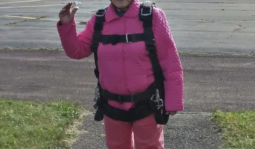 """This Sunday, Oct. 22, 2017, photo provided by Eric Fox shows Eila Campbell, of Williamsport, Pa., waving as she celebrates her 94th birthday by going skydiving with her granddaughter and great-granddaughter at Above the Poconos Skydivers at Hazleton Regional Airport in Hazleton, Pa. Each woman jumped separately but in tandem with an instructor, and Campbell described the free fall as """"kind of a wow"""" and says she'd skydive again. (Eric Fox via AP)"""