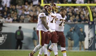 Washington Redskins offensive tackle Morgan Moses, center, is helped off the field by offensive tackle Trent Williams, left, and offensive guard Brandon Scherff during the first half of an NFL football game against the Philadelphia Eagles, Monday, Oct. 23, 2017, in Philadelphia. (AP Photo/Matt Rourke)