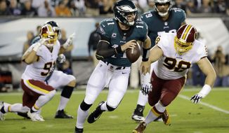 Philadelphia Eagles quarterback Carson Wentz (11) scrambles as Washington Redskins defensive tackle Matthew Ioannidis (98) chases him during the first half of an NFL football game, Monday, Oct. 23, 2017, in Philadelphia. (AP Photo/Michael Perez)