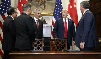 President Donald Trump and Singapore's Prime Minister Lee Hsien Loong talk with Singapore Airlines CEO Goh Choon Phong, second from left, and Kevin McAllister, president and chief executive officer of Boeing Commercial Airplanes,right, after they signed a contract in the Roosevelt Room of the White House, Monday, Oct. 23, 2017, in Washington. (AP Photo/Evan Vucci)
