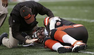 This Sunday, Oct. 22, 2017, photo shows a trainer checking Cleveland Browns tackle Joe Thomas after Thomas was hurt in the second half of an NFL football game against the Tennessee Titans, in Cleveland. The Browns are awaiting tests on Pro Bowl tackle Joe Thomas, whose season may be over because of a triceps injury. Thomas was hurt during the third quarter of Sunday's overtime loss to Tennessee, ending his streak of consecutive snaps at 10,363. He had been on the field for every offensive play of his career since 2007 before an injury that left teammates, fans and Titans players shaken. (AP Photo/Ron Schwane)