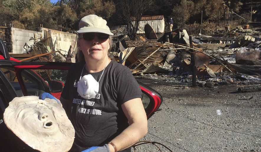 Joyce Farinato, a pastor and artist who lost her Glen Ellen, Calif., home in recent wildfires, stands in the ruins Monday, Oct. 23, 2017, and shows a mask she found in the debris, one of her few surviving possessions. Farinato said she wants to follow the environmental rules on cleaning burned sites but needs to know what they are. (AP Photo/Ellen Knickmeyer)