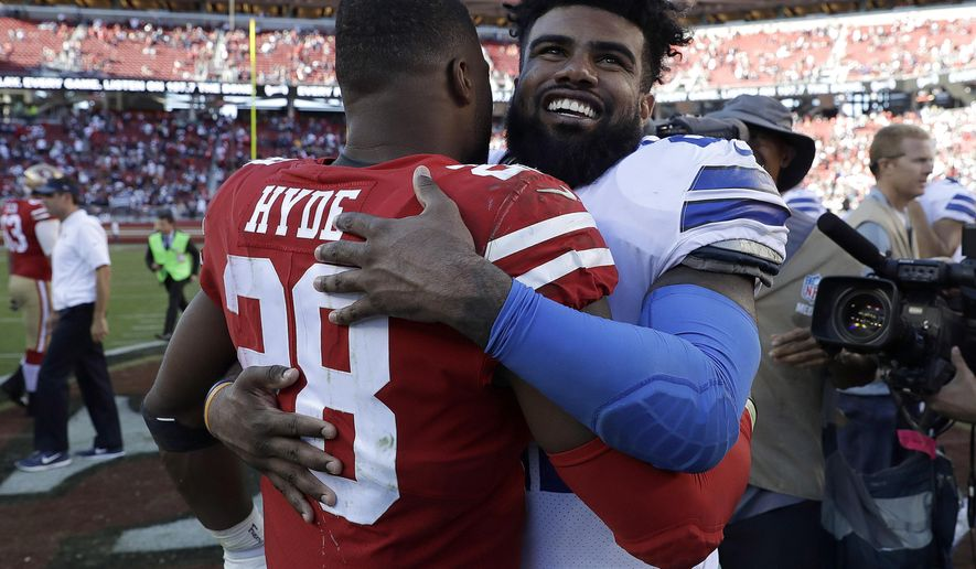 San Francisco 49ers running back Carlos Hyde (28) hugs Dallas Cowboys running back Ezekiel Elliott after the Cowboys beat the 49ers in an NFL football game in Santa Clara, Calif., Sunday, Oct. 22, 2017. (AP Photo/Marcio Jose Sanchez)