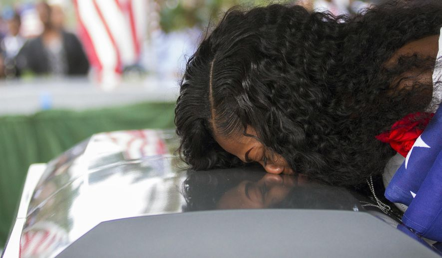 In this Saturday, Oct. 21, 2017, file photo, Myeshia Johnson kisses the casket of her husband, Sgt. La David Johnson during his burial service at Fred Hunter's Hollywood Memorial Gardens in Hollywood, Fla. (Matias J. Ocner/Miami Herald via AP, File)