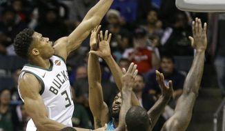 Milwaukee Bucks' Giannis Antetokounmpo shoots over the arms of three Charlotte Hornets during the first half of an NBA basketball game, Monday, Oct. 23, 2017, in Milwaukee. (AP Photo/Tom Lynn)