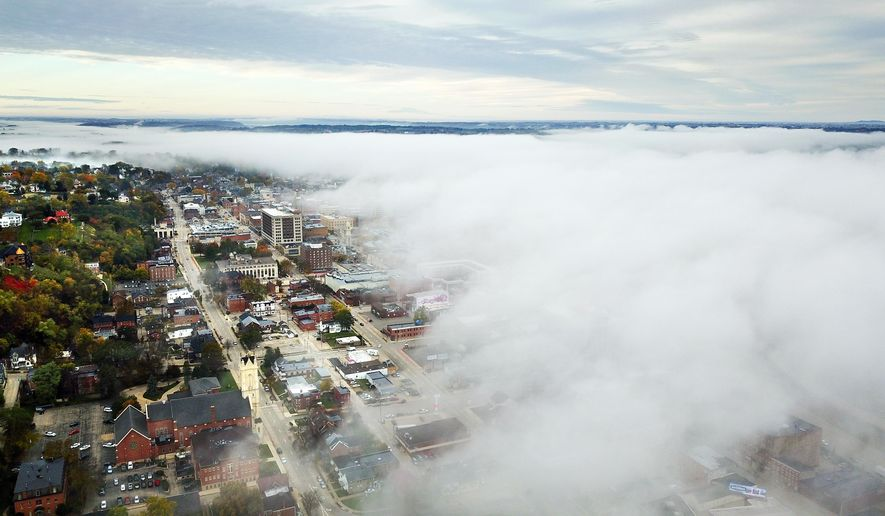 A thick layer of fog rolls over the Mississippi River toward Dubuque, Iowa, Monday, Oct. 23, 2017. (Dave Kettering/Telegraph Herald via AP)