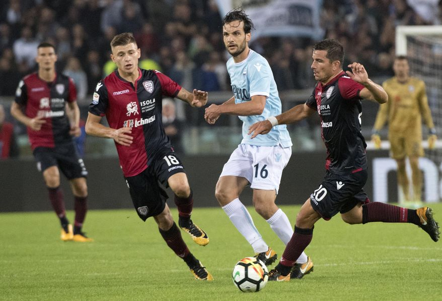 Cagliari's Nicol' Barella, Lazio's Marco Parolo and Cagliari's Simone Padoin vie for the ball during Serie A soccer match between Lazio and Cagliari, at the Olimpico Stadium in Rome, Sunday, Oct. 22, 2017. (Claudio Peri/ANSA via AP)