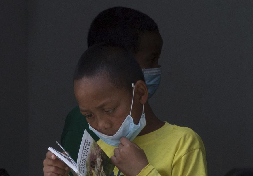 FILE -- In this file photo taken Tuesday Oct. 10, 2017, a girl wears a face mask inside a hospital in the capital Antananarivo, Madagascar. Action Against Hunger said Monday. Oct. 23, 2017 that 102 plague deaths have been reported since the outbreak began in August and that most of the nearly 1,300 reported cases of plague are of the pneumonic kind, a more virulent form that spreads through coughing, sneezing or spitting and is almost always fatal if untreated. (AP Photo/Alexander Joe, File)