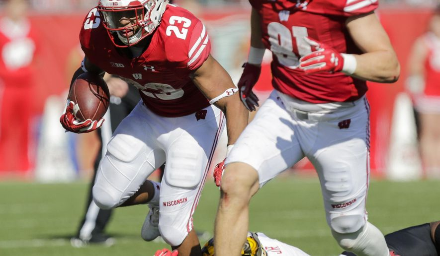 Wisconsin running back Jonathan Taylor (23) runs past Maryland linebacker Jermaine Carter as Wisconsin's Troy Fumagalli looks to block during the second half of an NCAA college football game Saturday, Oct. 21, 2017, in Madison, Wis. Wisconsin 38-14. (AP Photo/Andy Manis)
