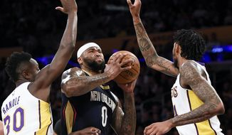 New Orleans Pelicans center DeMarcus Cousins, center, drives the ball between Los Angeles Lakers forward Julius Randle, left, and guard Brandon Ingram during the first half of an NBA basketball game in Los Angeles, Sunday, Oct. 22, 2017. (AP Photo/Kelvin Kuo)