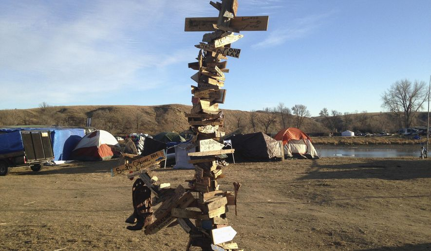 "This Nov. 26, 2016, photo shows a mile-marker post created by activists near Cannon Ball, N.D., during protests against the Dakota Access pipeline. The Smithsonian Institution's National Museum of the American Indian in Washington, D.C., is adding the 12-foot-tall marker to its exhibit on treaties called ""Nation to Nation: Treaties Between the United States and American Indian Nations."" (AP Photo/James MacPherson)"