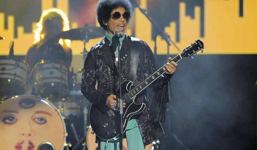 FILE - In this May 19, 2013, file photo, Prince performs at the Billboard Music Awards at the MGM Grand Garden Arena in Las Vegas. Three Indiana pharmacists have been reprimanded for trying to access Prince's medical records within days of the superstar's death last year. Prince died April 21, 2016, of an accidental overdose of the painkiller fentanyl. (Photo by Chris Pizzello/Invision/AP, File)