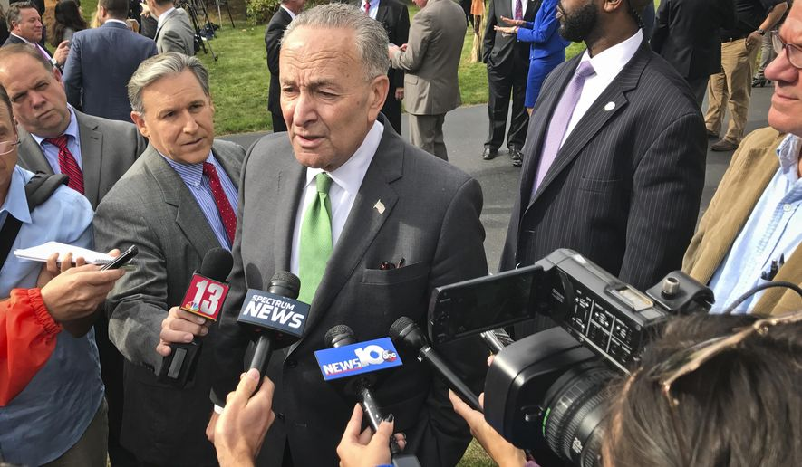 U.S. Sen. Charles Schumer, center, address reporters after holding a news conference with New York Gov. Andrew Cuomo, denouncing a tax overhaul plan from Republicans and called on the state's GOP lawmakers to reject it Monday, Oct. 23, 2017, in Bethlehem, N.Y. (AP Photo/David Klepper)