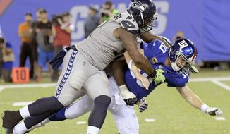 Seattle Seahawks' Sheldon Richardson, left, tackles New York Giants quarterback Eli Manning during the second half of an NFL football game, Sunday, Oct. 22, 2017, in East Rutherford, N.J. (AP Photo/Bill Kostroun)