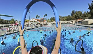 Swim instructor Daphne Trager leads an exercise session at Rose Bowl Aquatics Center in Pasadena, Calif., Monday, Oct. 23, 2017. Temperatures in some parts of Southern California climbed into the upper 90s and over 100 on Monday as authorities warned of several days of dangerously high heat plus gusty Santa Ana winds that boost the risk of wildfires. (Walt Mancini/Los Angeles Daily News via AP)