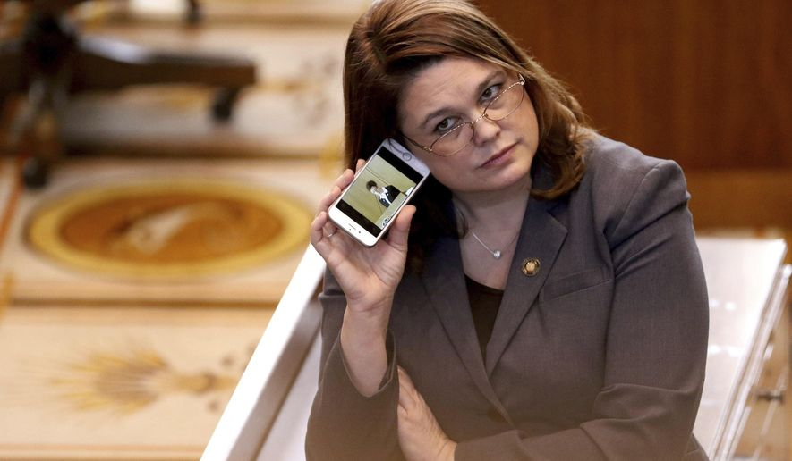 FILE - In this March 3, 2016, file photo, Oregon state Sen. Sara Gelser, D-Corvallis, listens to a live stream as members of the House of Representatives finish business before adjourning the 2016 legislative session at the Oregon State Capitol in Salem, Ore. Democratic Sen. Gelser, who accused Republican Sen. Jeff Kruse of inappropriate touching, said Monday, Oct. 23, 2017, she heard accounts from other women in the Oregon State Capitol of such behavior by men. (Anna Reed/Statesman-Journal via AP, File)
